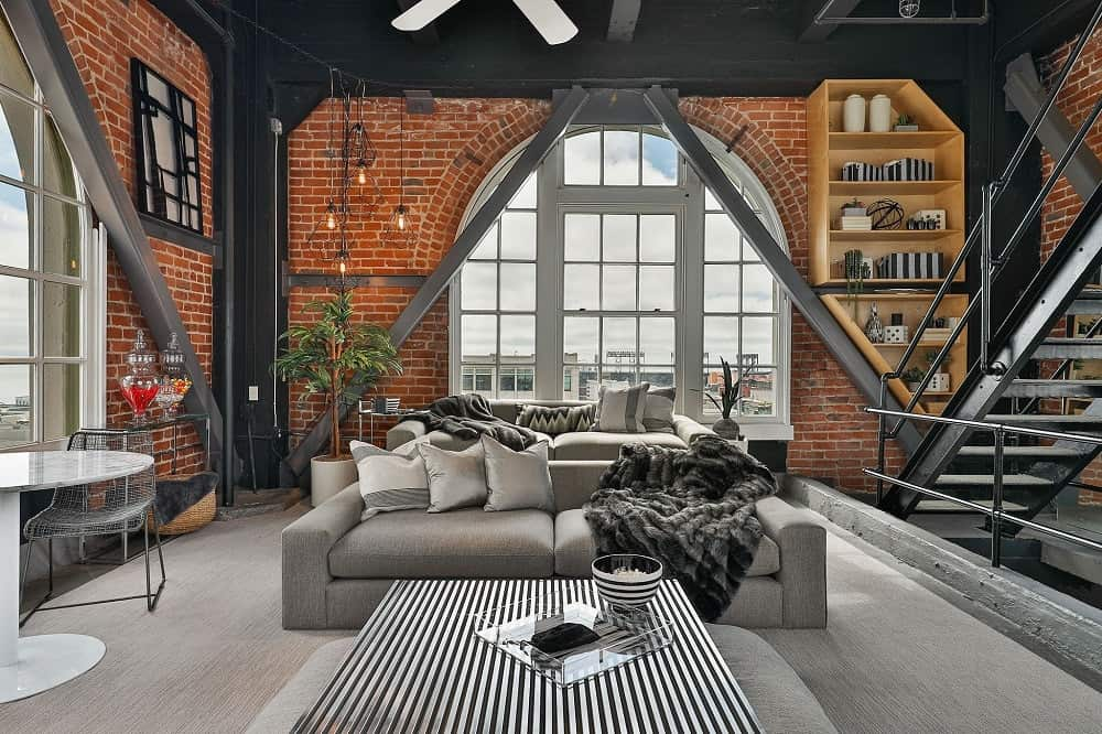 This game room has a comfortable gray sofa, a large coffee table and tall red brick walls. Images courtesy of Toptenrealestatedeals.com.