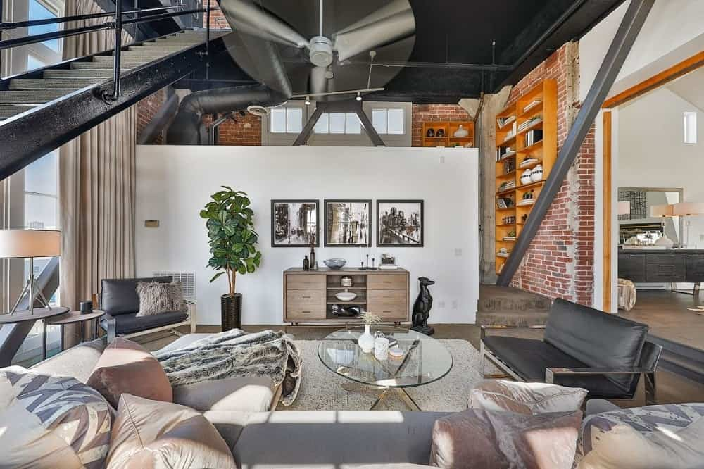 The living room boasts of an Industrial-style aesthetic with tall brick walls. Images courtesy of Toptenrealestatedeals.com.