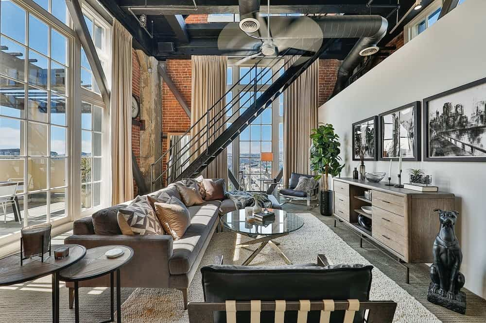 Side angle view of the living room shows the metal staircase beside it that adds to its Industrial-style beauty. Images courtesy of Toptenrealestatedeals.com.