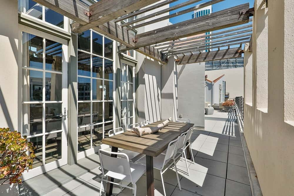 The outdoor dining area has a large rectangular dining table shaded by wooden beams above and surrounded by white outdoor chairs. Images courtesy of Toptenrealestatedeals.com.