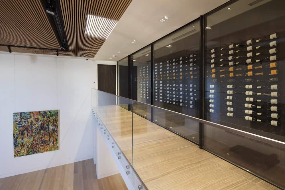 The narrow hallway with an indoor balcony overlooking the art gallery below has a glass enclosed wall with a collection of wine bottles on display. Images courtesy of Toptenrealestatedeals.com.