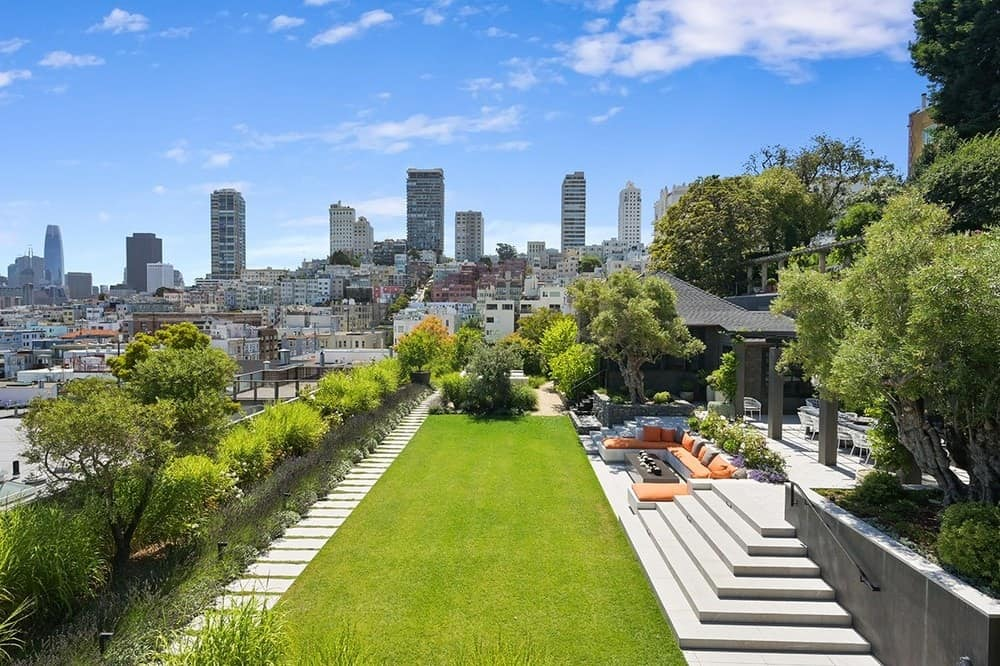 The gorgeous backyard has a large lawn of lush green grasssurrounded by shrubbery and tall trees and has a perfect view of the skyline. Images courtesy of Toptenrealestatedeals.com.