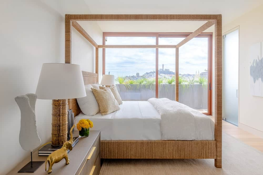 The second bedroom has a rustic and lovely wooden four-poster bed that pairs quite well with the bedside drawers and the table lamp on it that stands out against the bright tone of the wall. Images courtesy of Toptenrealestatedeals.com.