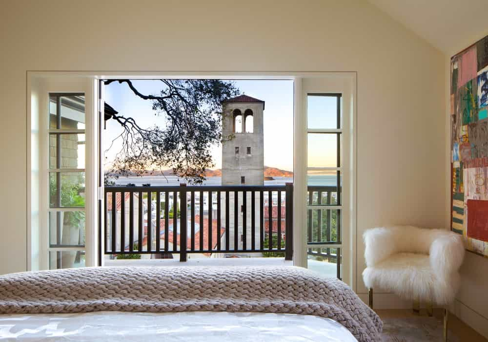 The third bedroom has a bed facing a wide set of French glass doors with a beautiful view of the bell tower in the distance amidst rooftops and tall trees. Images courtesy of Toptenrealestatedeals.com.