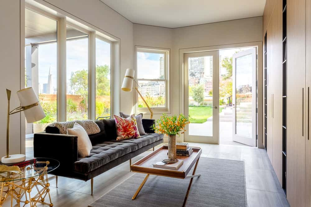 The simple den of the house has a long dark gray cushioned couch with pillows and paired with a wooden rectangular coffee table on a gray area rug. All of these are brightened by the surrounding glass windows and glass doors. Images courtesy of Toptenrealestatedeals.com.