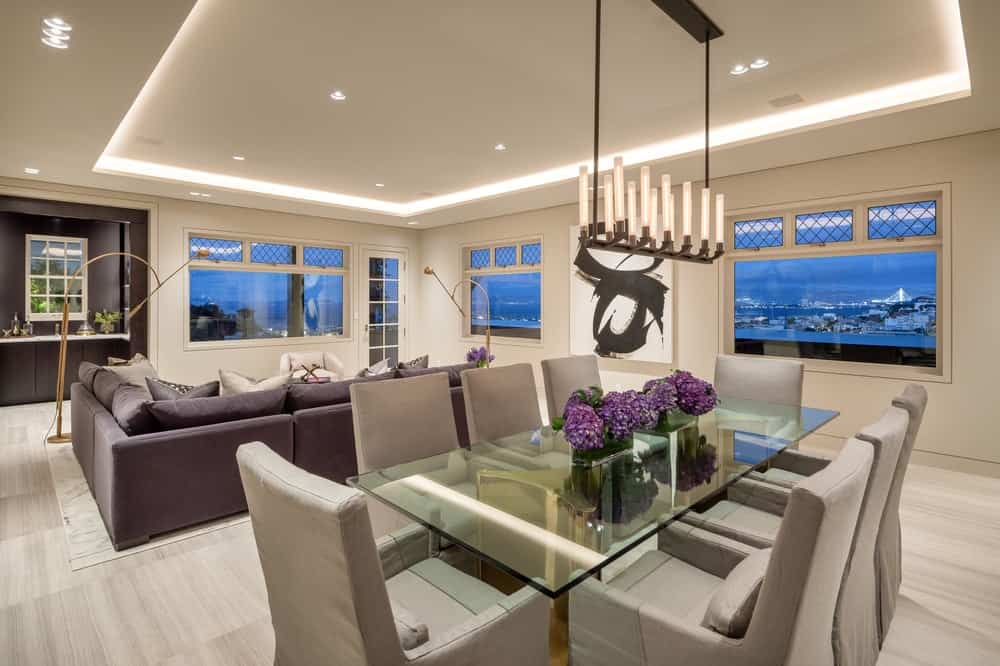 The glass-top dining table is topped with a beautiful centerpiece and a row of lights from the tray ceiling for a modern touch to the dining area. Images courtesy of Toptenrealestatedeals.com.