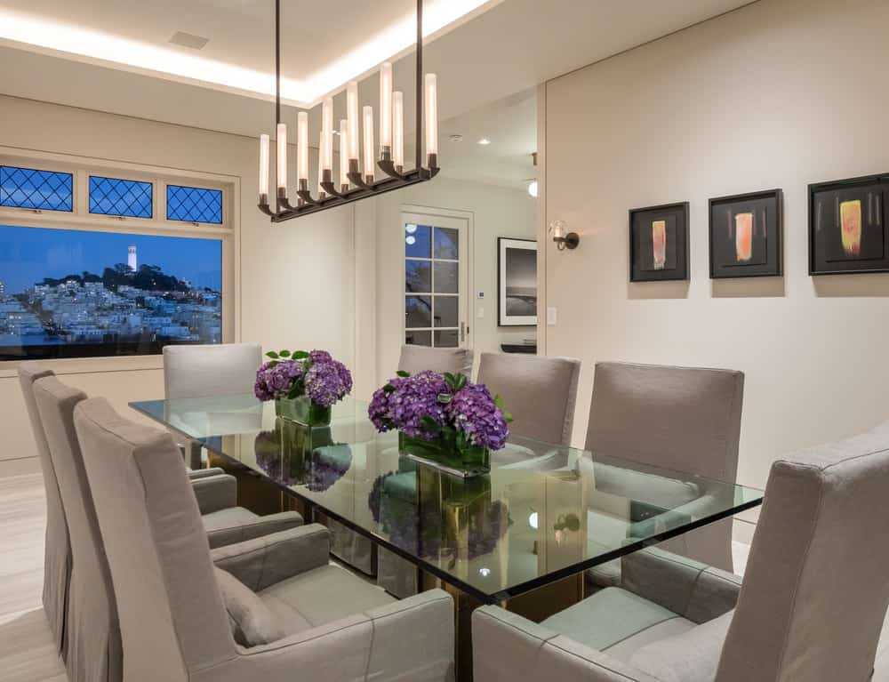 The luxurious dining room has a large glass-top rectangular dining table surrounded by gray cushioned dining chairs. Images courtesy of Toptenrealestatedeals.com.