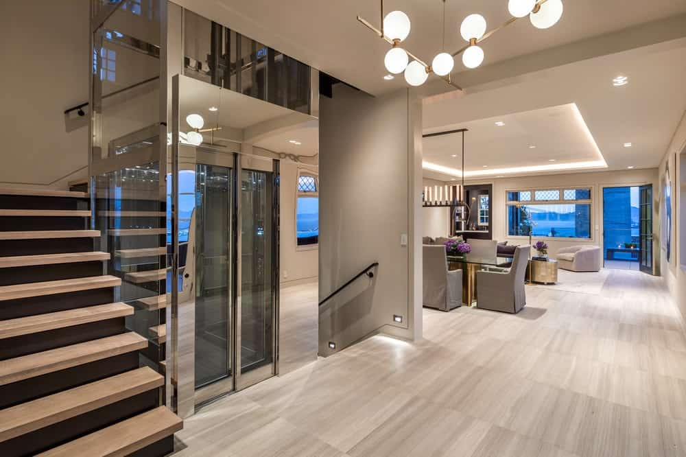 The foyer and main hall of this gorgeous home features its own glass-enclosed elevator wrapped around by the staircase with wooden steps. Images courtesy of Toptenrealestatedeals.com.