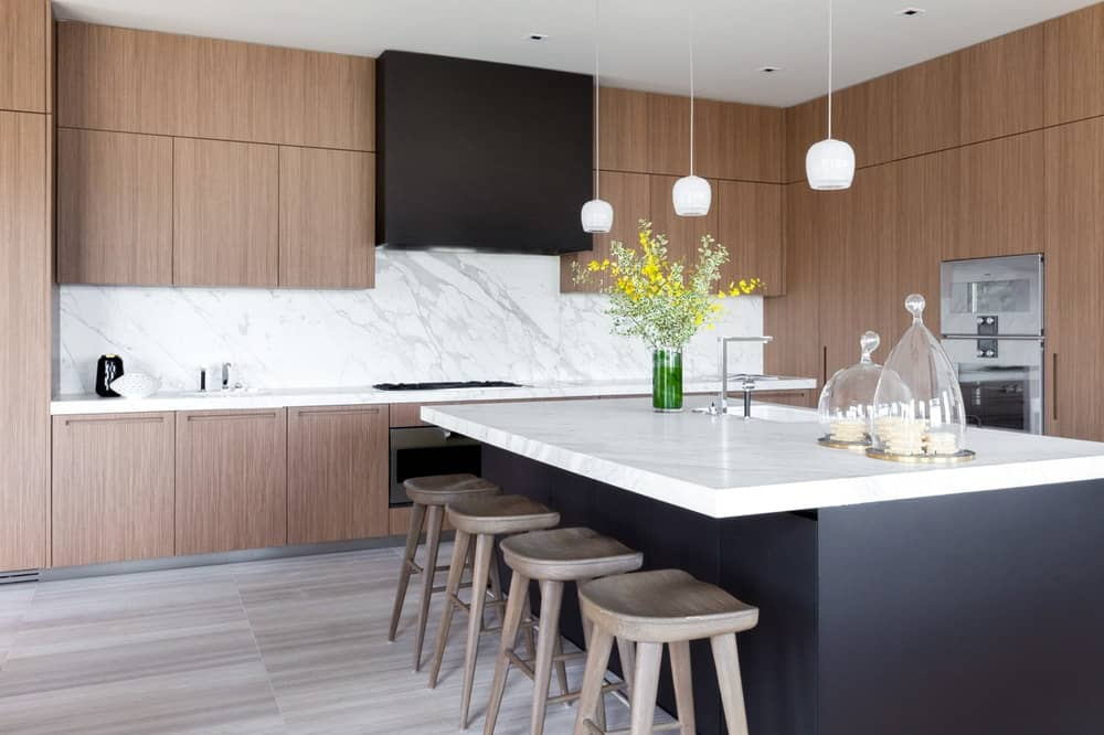 The kitchen island is paired with four wooden stools for the breakfast bar topped with small pendant lights. Images courtesy of Toptenrealestatedeals.com.