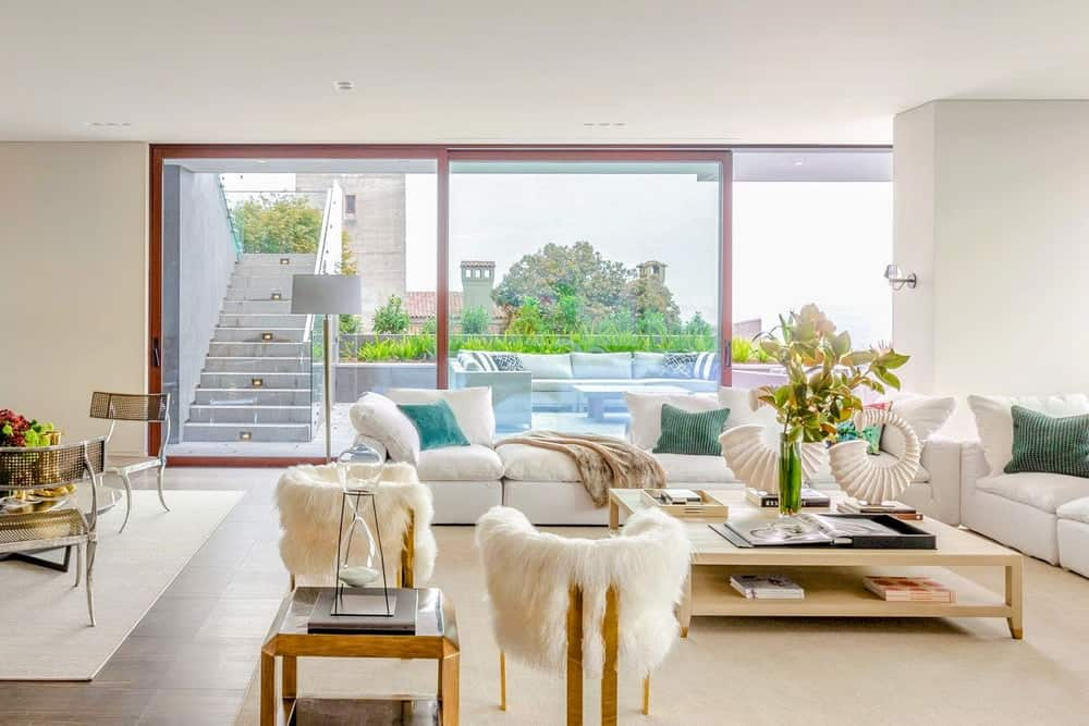 The bright living room has an abundance of natural lighting thanks to the wide glass windows with sliding glass doors augmented by the bright wall tones. Images courtesy of Toptenrealestatedeals.com.