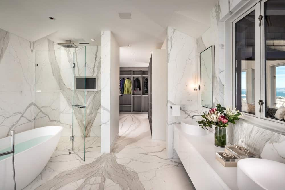 The primary bathroom has a bright and white aesthetic to its white marble floors and walls as well as a white floating vanity on one side with wall-mounted mirrors. Images courtesy of Toptenrealestatedeals.com.