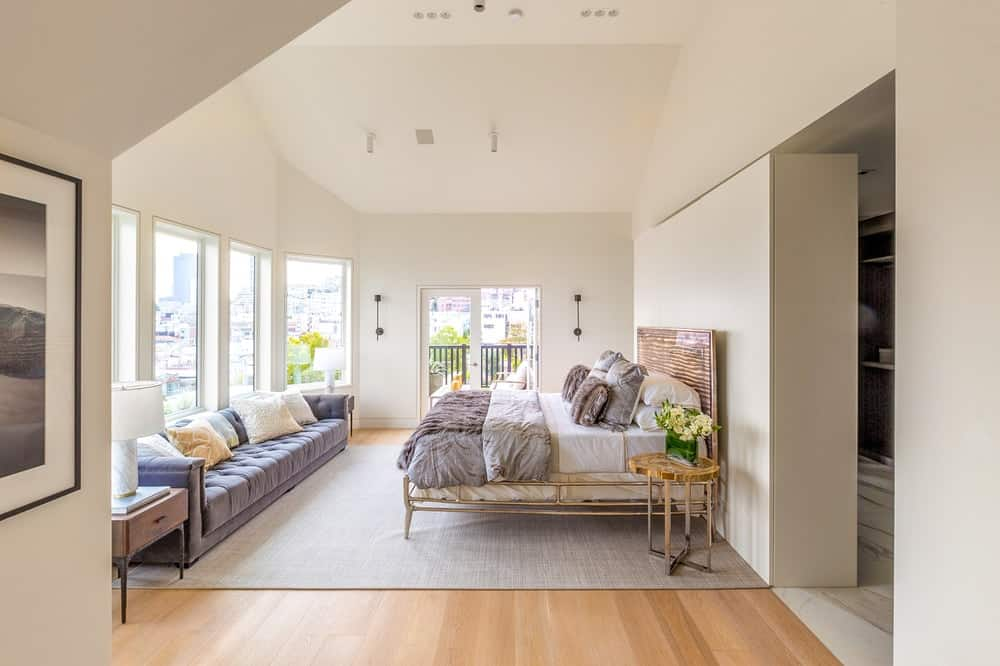 The gorgeous primary bedroom has a beige arched ceiling that fuses well with the beige walls complemented by the wooden headboard of the bed. Images courtesy of Toptenrealestatedeals.com.