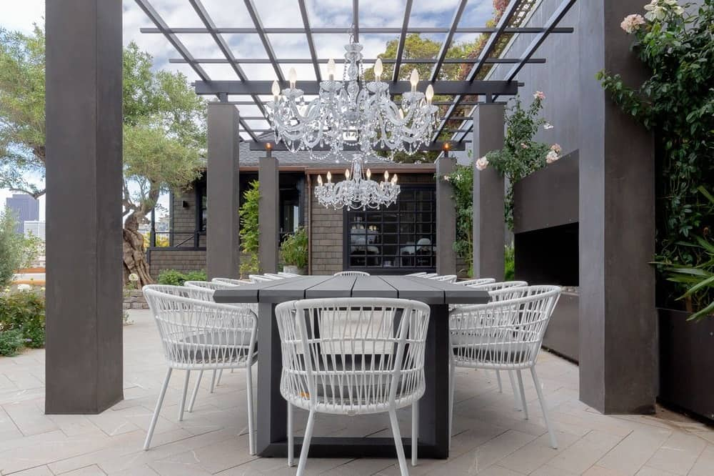 A closer look at the outdoor dining area shows that it has a large rectangular dining table surrounded by white garden chairs and topped with a majestic chandelier. Images courtesy of Toptenrealestatedeals.com.