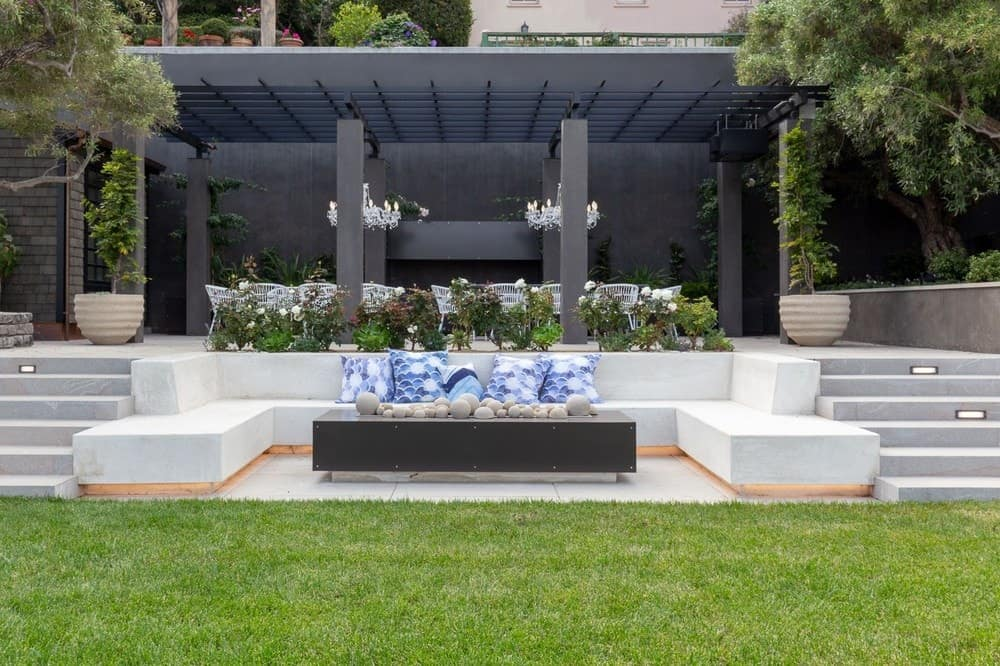 The backyard patio has its own firepit surrounded by built-in U-shaped stone bench adorned with plants and grass. Images courtesy of Toptenrealestatedeals.com.