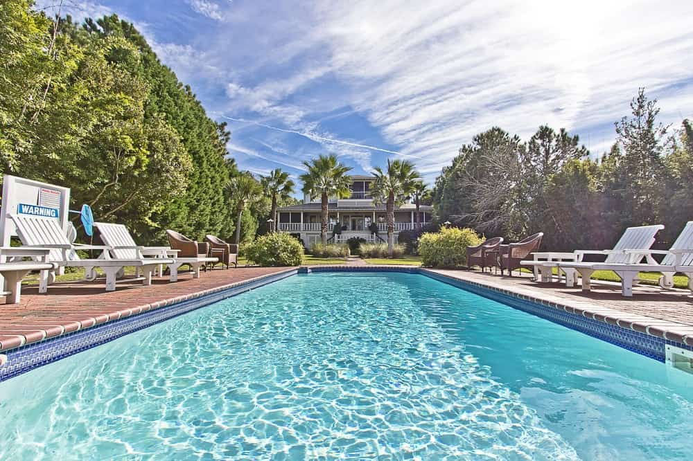 The large backyard dominated by the swimming pool is surrounded by a lavish and tall greenery that serves as a beautiful backdrop as well as for privacy. Images courtesy of Toptenrealestatedeals.com.