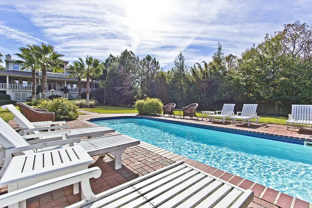 The backyard boasts of a large swimming pool that is surrounded by charming red brick walkways fitted with various lawn chairs for a relaxing day under the sun. Images courtesy of Toptenrealestatedeals.com.