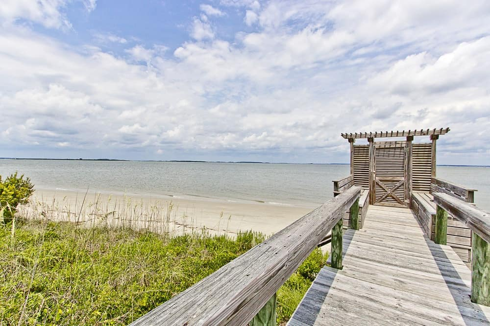 The beachfront of the house has a wooden walkway elevated from the beach for the high tide. This walkway is lined with rustic waist-high wooden railings for safety. Images courtesy of Toptenrealestatedeals.com.