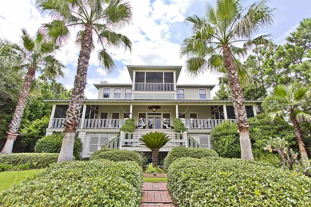 This lovely Beach-style home is adorned with a front yard filled with lush shrubbery and tall tropical trees that pair quite nicely with the bright and airy exteriors of the house that has abundant outdoor areas to boast. Images courtesy of Toptenrealestatedeals.com.
