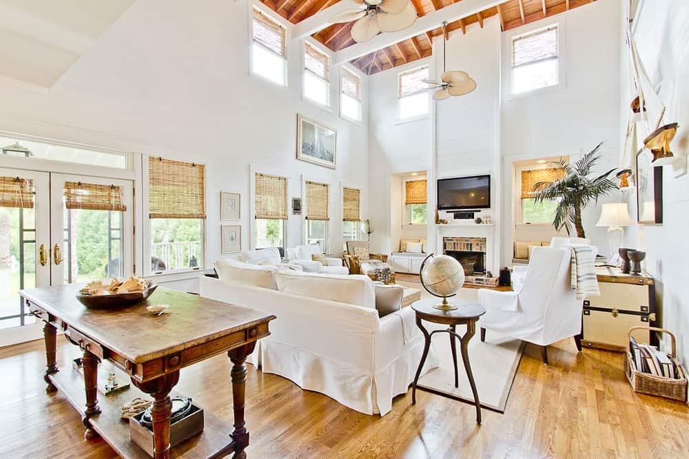 The bright and airy living room has a tall ceiling and a clean white Beach-house style feel to it. It has a fireplace warming up the sofa set covered in white that blends well with the walls and exposed wooden beams of the ceiling. Images courtesy of Toptenrealestatedeals.com.