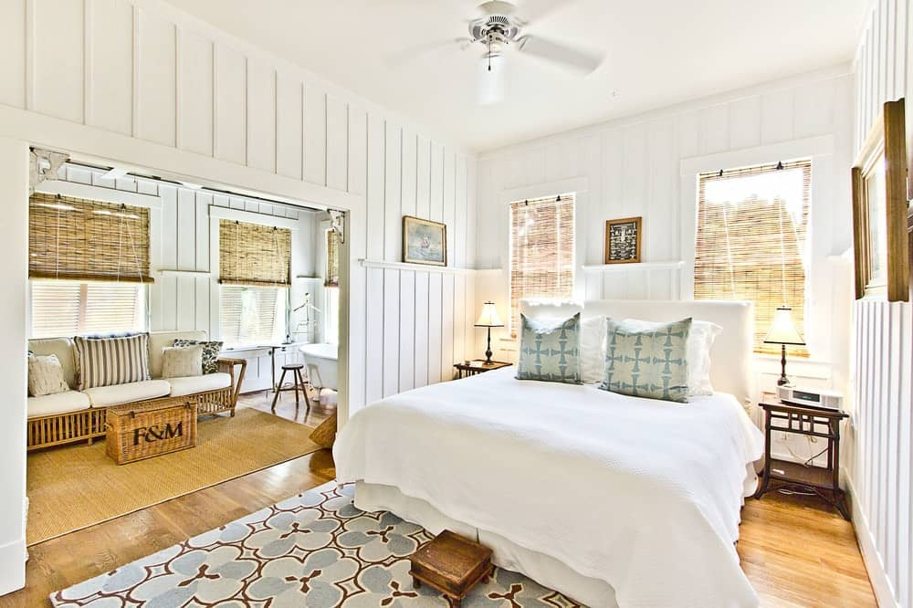 The primary bedroom has the same white and bright Beach-style aesthetic to it. It also has an open-wall entry to the bathroom with a freestanding bathtub by the window beside a comfortable wooden sofa. Images courtesy of Toptenrealestatedeals.com.