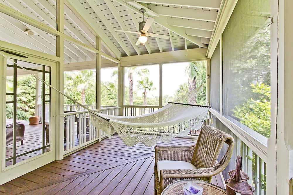 The comfortable patio has a relaxing white hammock with a great view of the surrounding tropical-style landscape scenery surrounding the house. There's also a set of woven wicker chairs for a sitting area. Images courtesy of Toptenrealestatedeals.com.