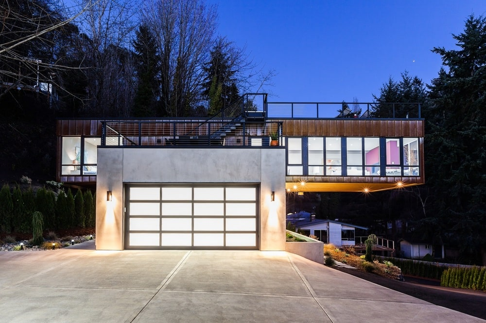 This is a front view of the contemporary-style home from the vantage of the concrete driveway leading to the garage door that matches the glass walls of the upper level.