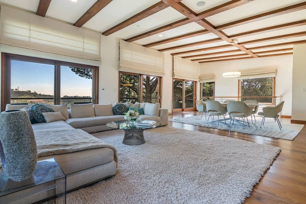 Large great room featuring a modish and comfy L-shaped sofa set on top of a large area rug.