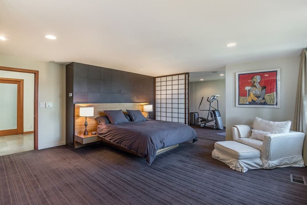 Large primary bedroom offering a modern cozy bed set lighted by table lamps on both sides. Images courtesy of Toptenrealestatedeals.com.