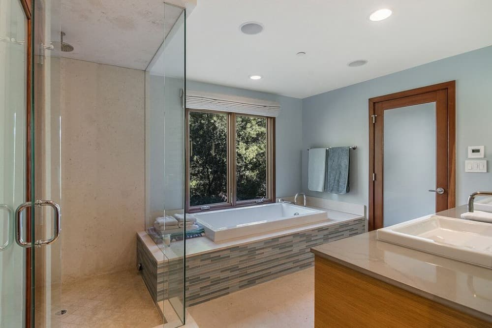 This bathroom offers a drop-in soaking tub by the window and a walk-in shower room, along with a double sink counter. Images courtesy of Toptenrealestatedeals.com.