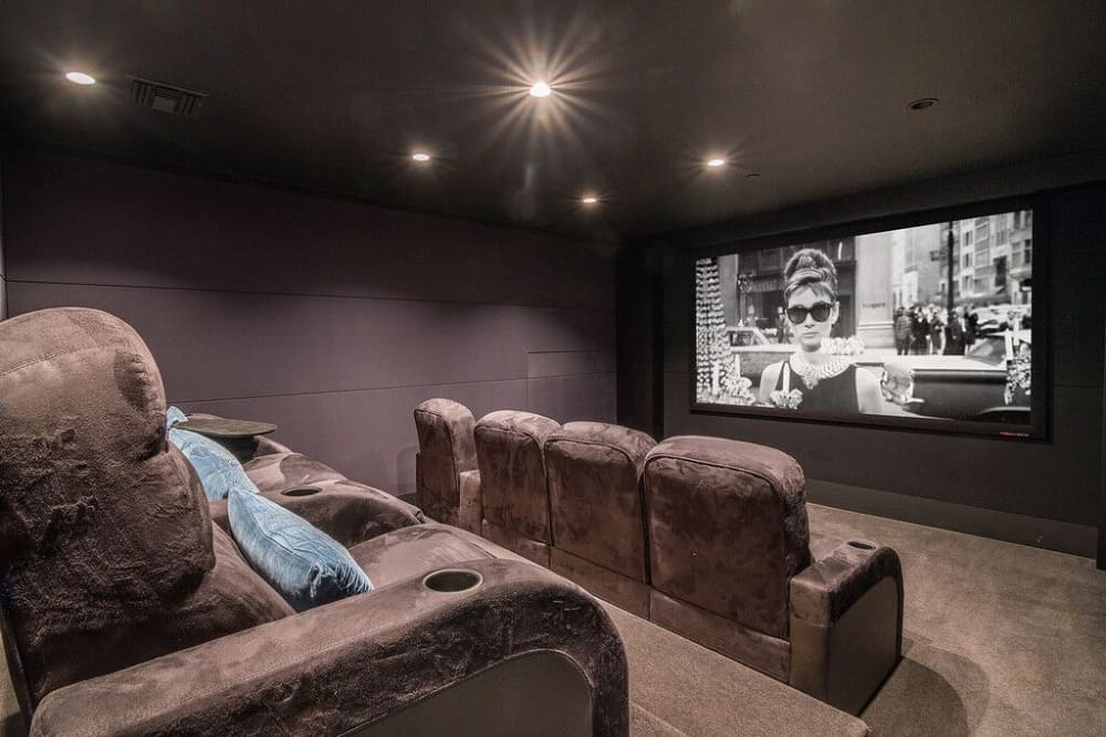Home theater featuring gray walls and carpeted flooring. The room offers cozy sectional theater seats and is lighted by recessed ceiling lights. Images courtesy of Toptenrealestatedeals.com.