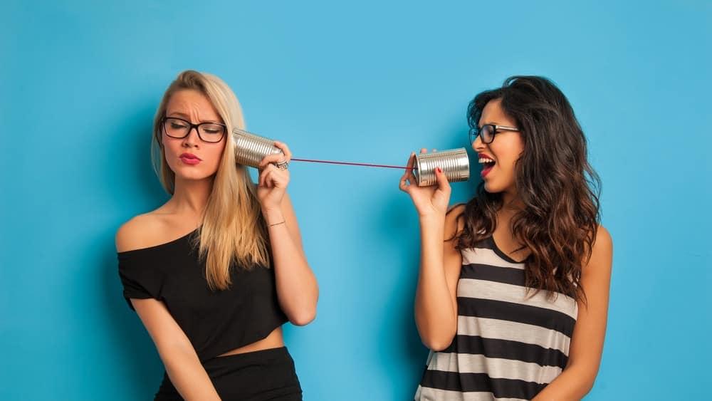 A couple of women talking through tin can telephones.