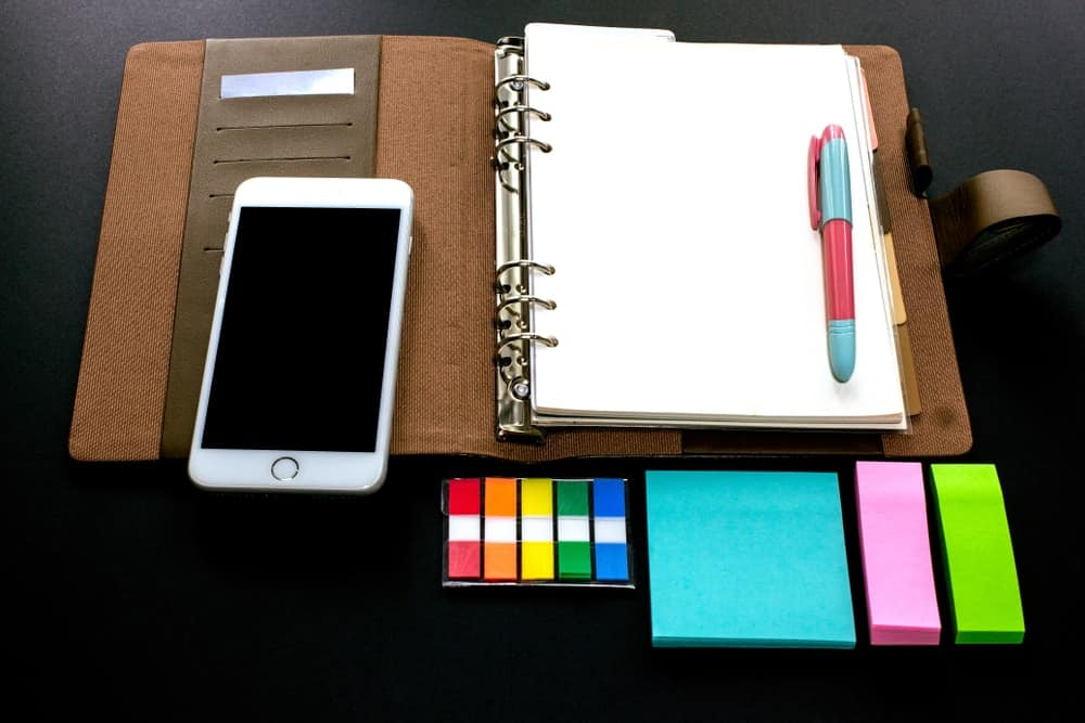 A mobile phone, planner and a variety of colorful sticky notes on a dark surface.