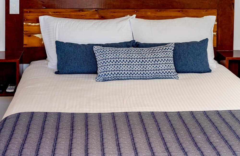 A freshly made bed that has a wooden headboard.