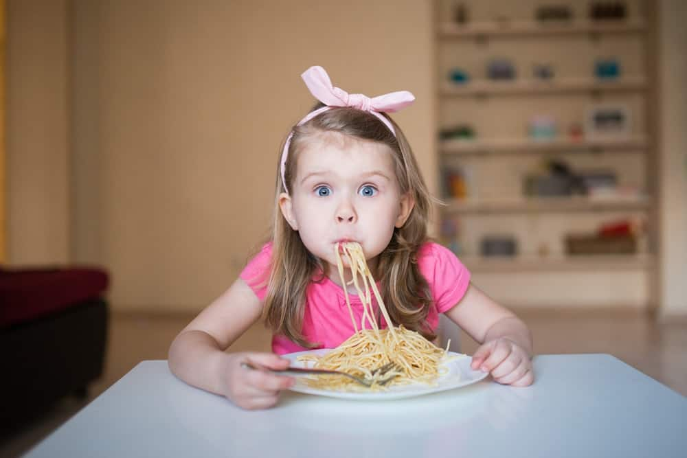 A young girl with spaghetti in her mouth.