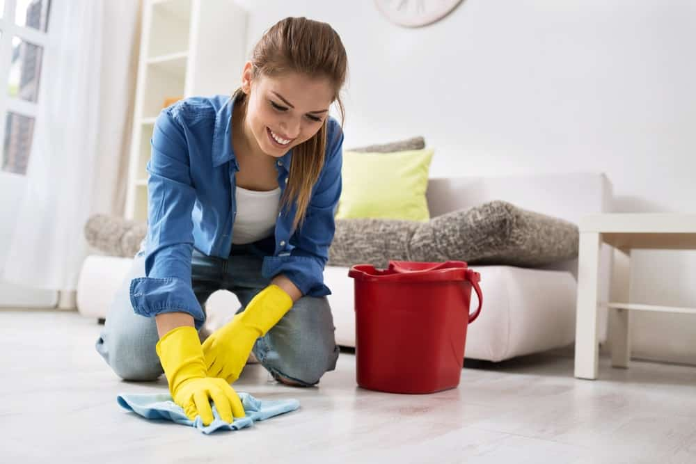 A smiling woman wiping the light-toned flooring of the living room.