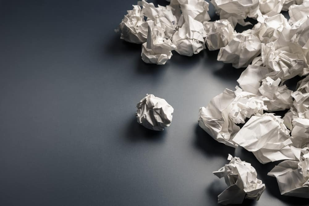 A bunch of crumpled paper on a black surface.