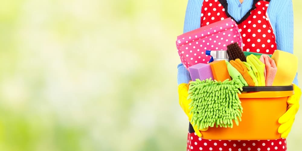 A woman carrying a bucket of various cleaning materials.