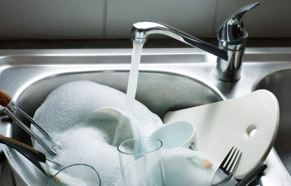 A kitchen sink filled with dishware being washed.