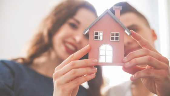 A couple holding a small model of a house.