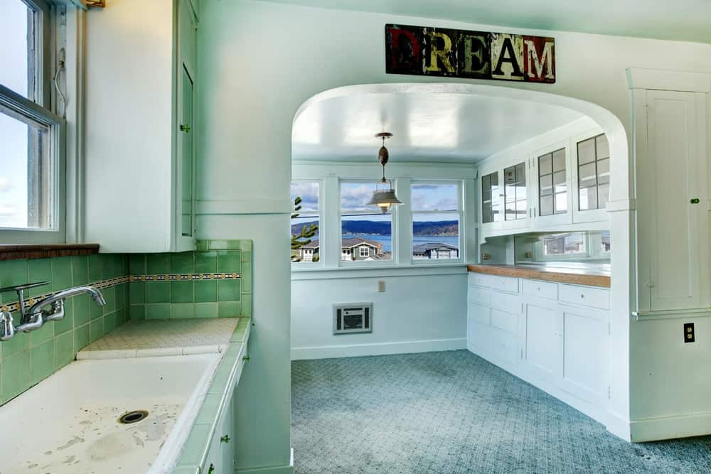 A kitchen with green walls and green cabinetry adorned with a word art above the archway.
