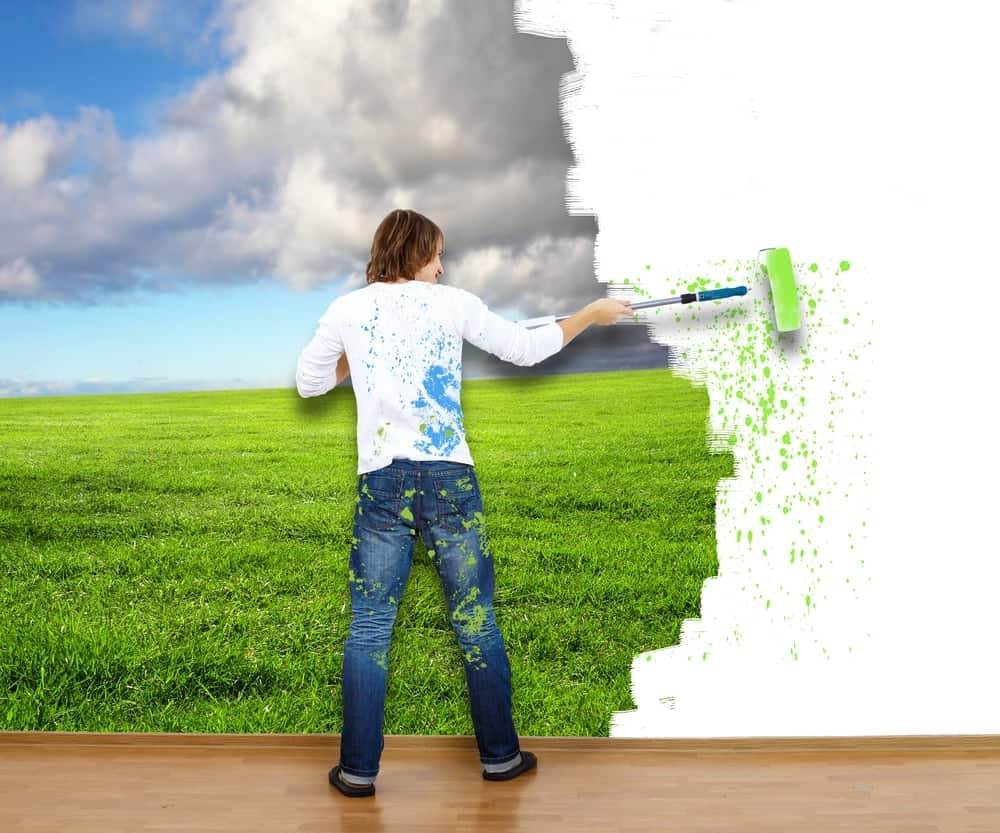 A man painting a mural of a cloudy plain onto a white wall.
