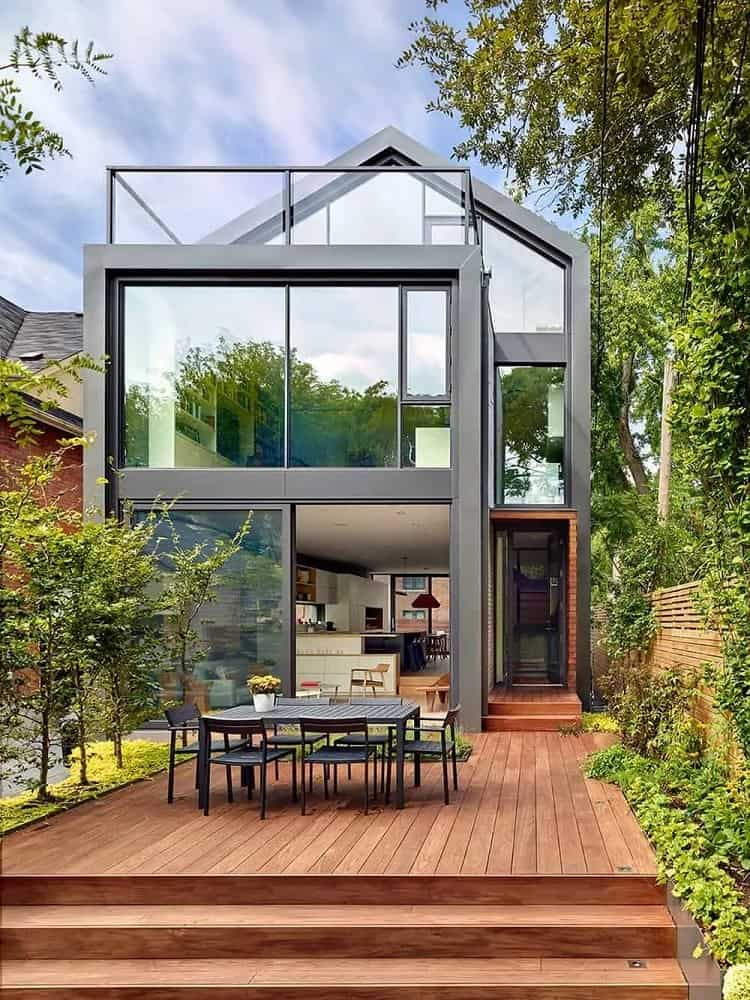 This is a look at the back of the house that is dominated by glass walls. These are complemented by the wooden deck floor of the backyard flanked by lush landscaping and topped with a gray outdoor dining set.