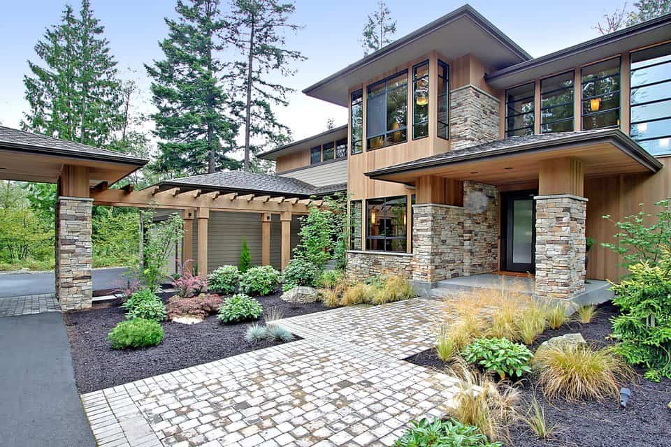 Angled view of the house with nice wood cladding accented with stone bricks. A brick pathway leads to the entry door.