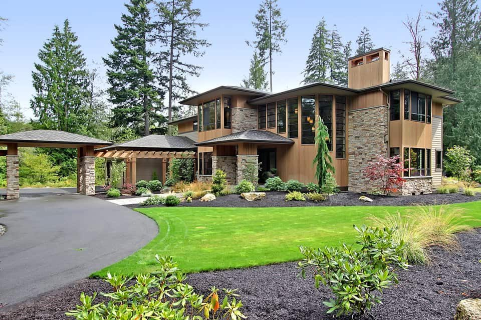 Beautiful wood siding accentuated with striking stones embellishes this two-story Northwest home. Sleek windows give a modern appeal while a pergola walkway leading to the main entrance creates a great impression.