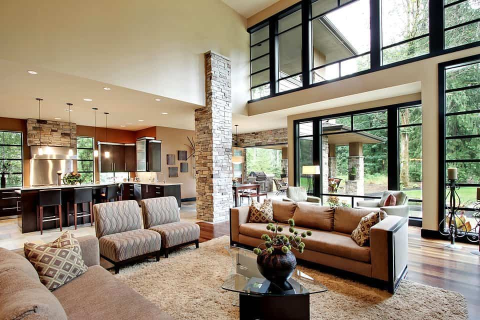 The living room has cozy seats and a glass top coffee table. It features a soaring ceiling and it opens out to the kitchen.