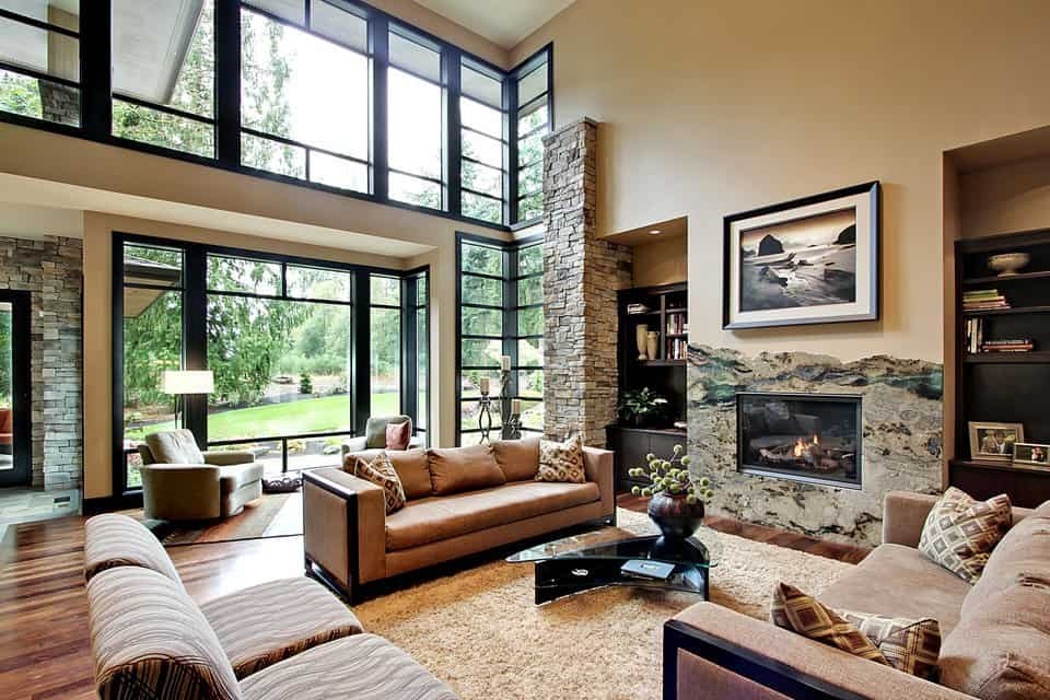 This view shows the modern fireplace and full height glazing overlooking the outdoor greenery.