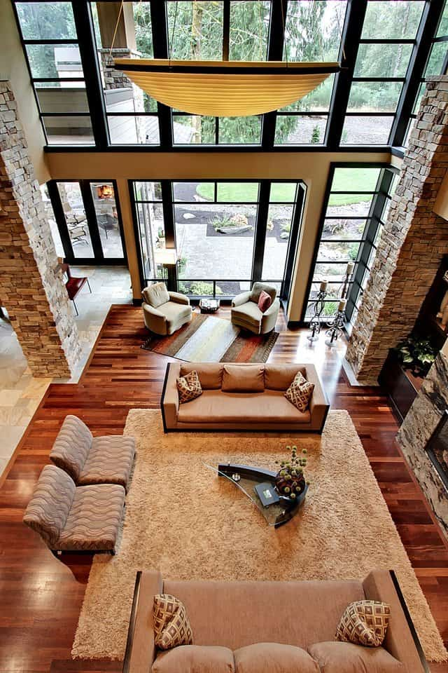 View of the living room from the upstairs balcony. It is warmed by ambient lighting and rich hardwood flooring.