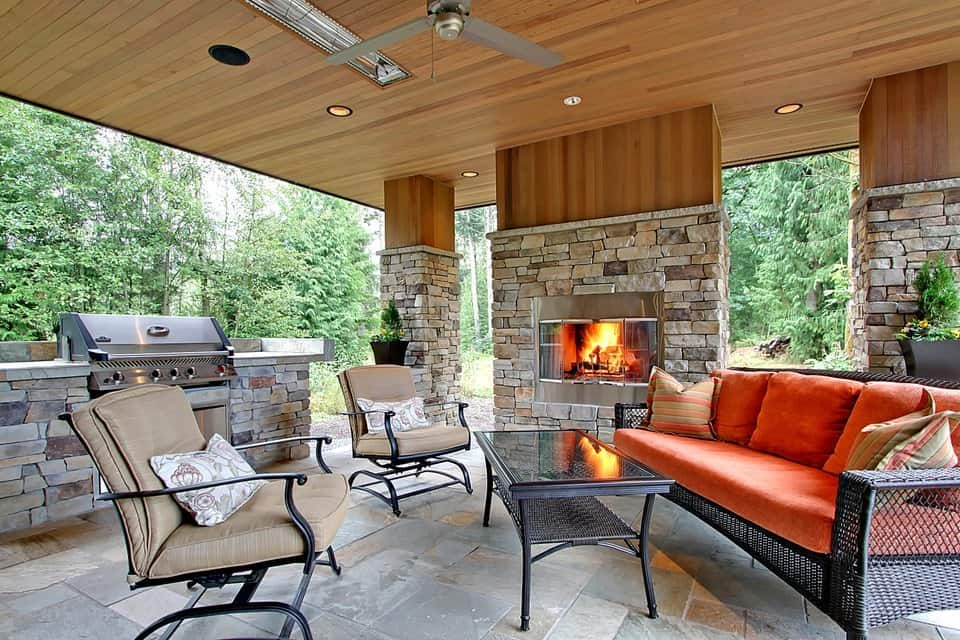 The outdoor living is filled with cushioned seats, an outdoor kitchen and a glass-enclosed fireplace flanked by stone columns.