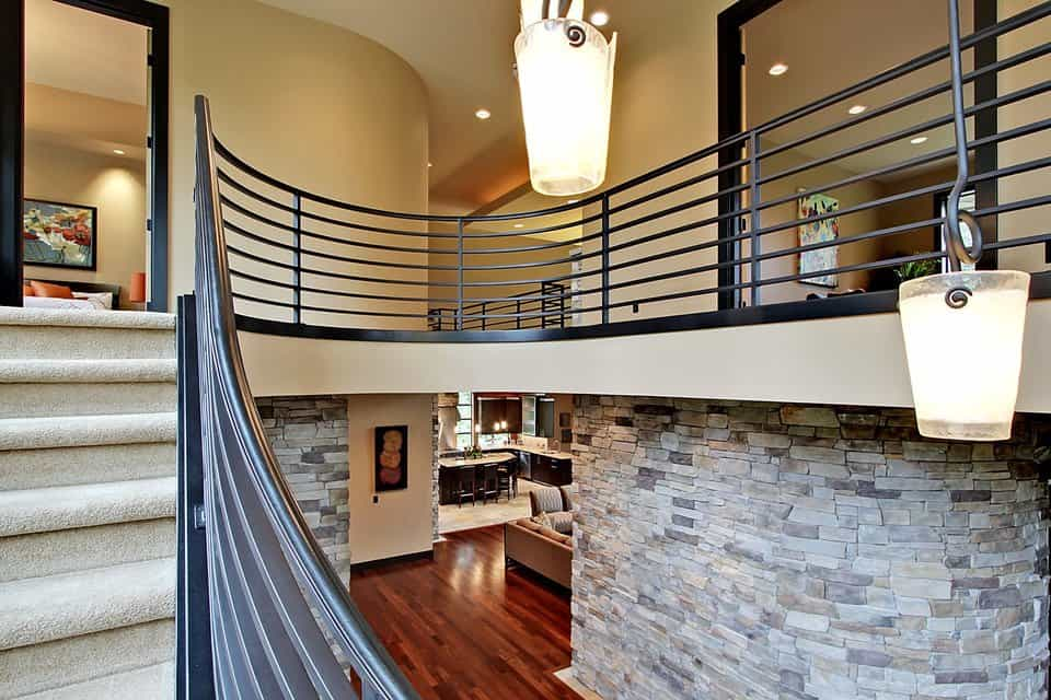 The balcony upstairs framed with metal railings and supported by stone pillars.