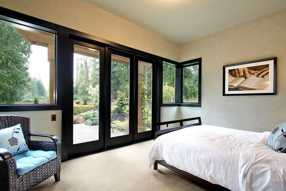 The guest suite has a wicker armchair and a dark wood bed facing the french doors that open out to the terrace.